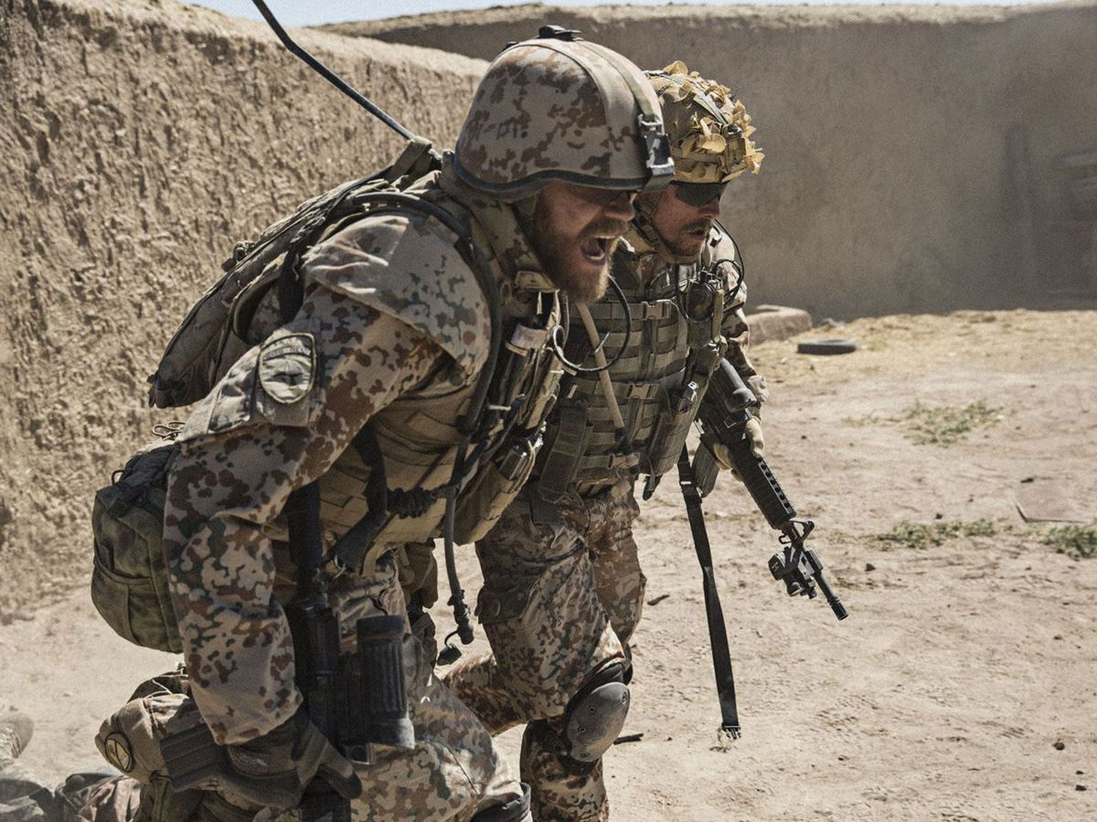 Two soldiers help each other across a battlefield.