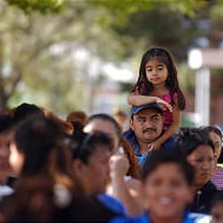 Five-year-old Yolanda rests atop the shoulders of her father as the two wait in lines with hundreds of others to attend a health fair at Central Middle School in Ogden. They emigrated from Mexico in 2003.