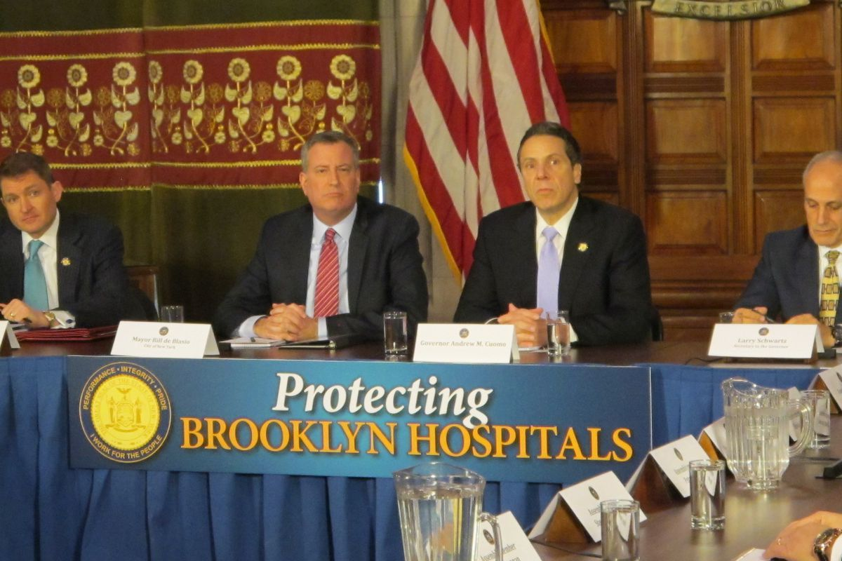 Bill de Blasio and Andrew Cuomo at a press conference in Albany discussing Brooklyn hospitals. The duo played down tension around their competing visions for funding universal pre-kindergarten.