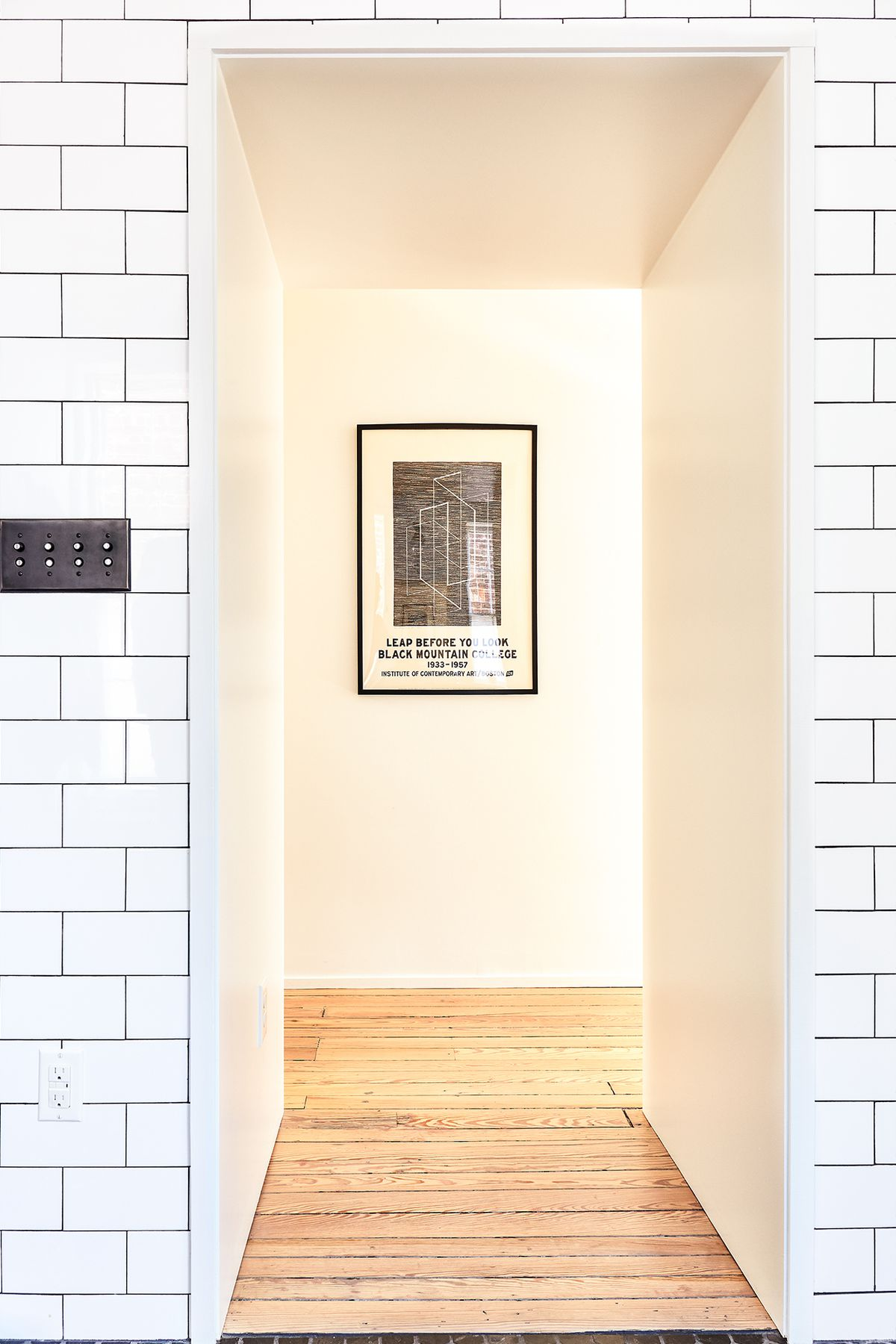 A hallway. The wall is covered in white tiles and the floor is hardwood. There is a framed poster at the end of the hallway.