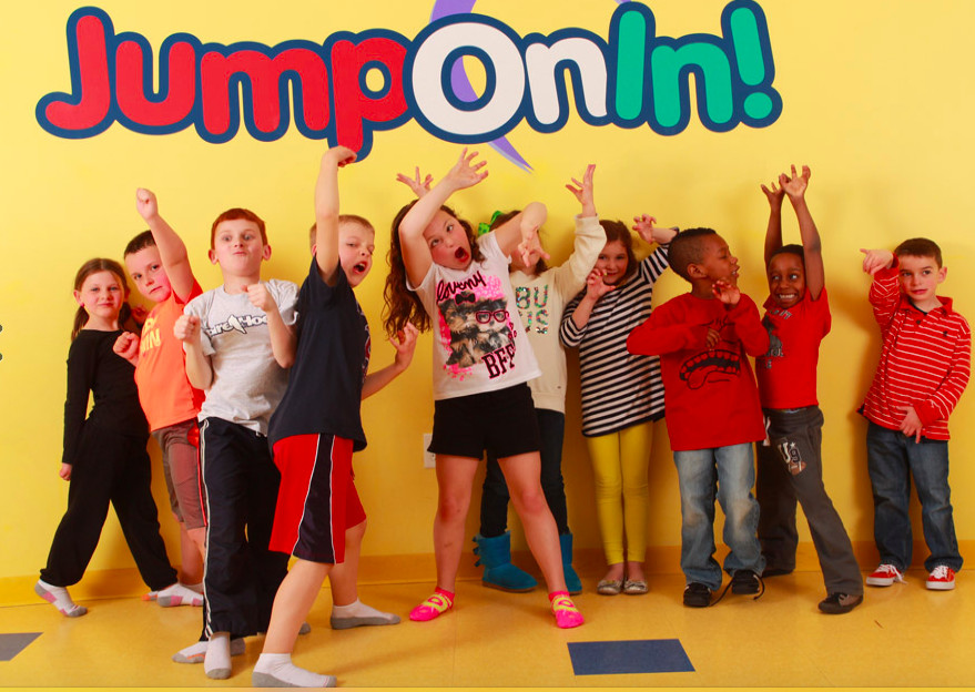 A row of kids making funny faces against an inflatable backdrop.
