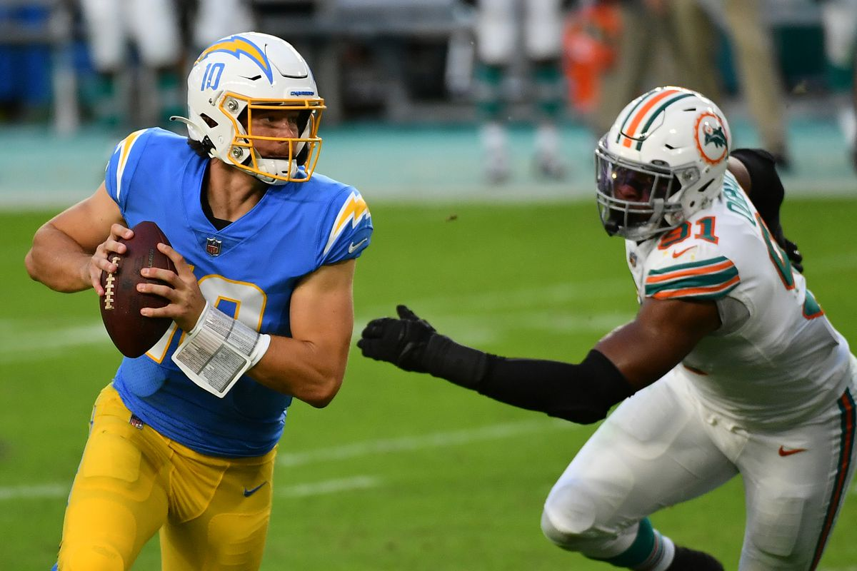 Los Angeles Chargers quarterback Justin Herbert (10) scrambles with the ball away from Miami Dolphins defensive end Emmanuel Ogbah (91) during the first half at Hard Rock Stadium.