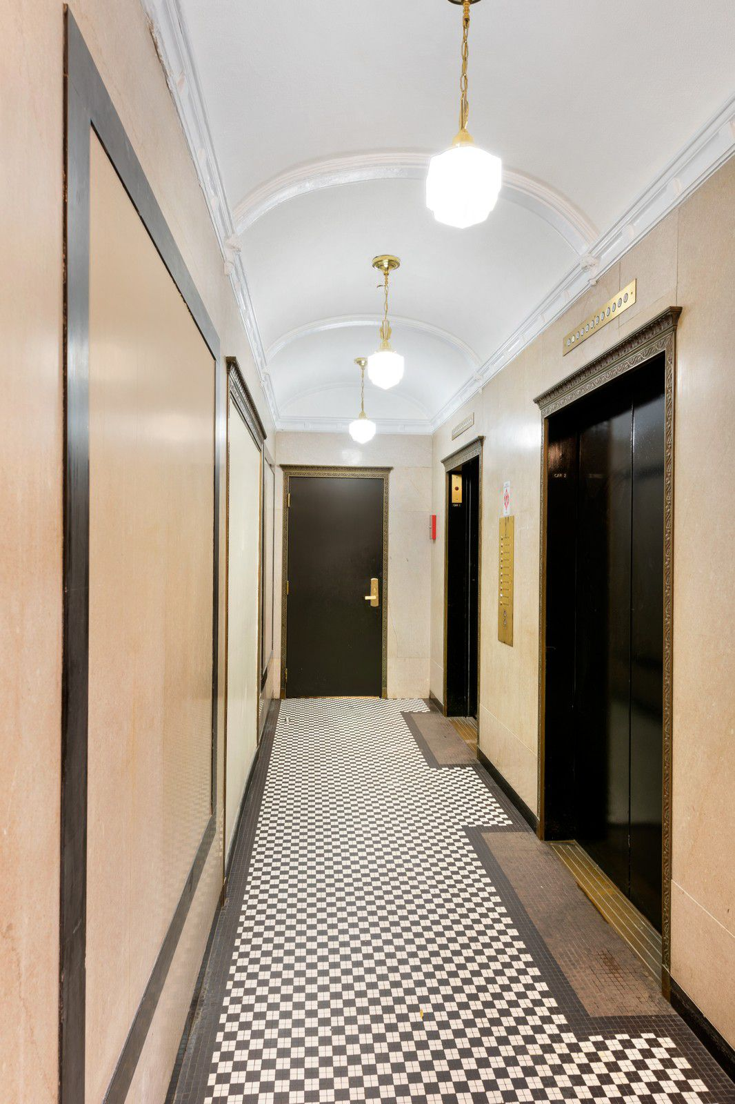 An elevator bank with a checkerboard floor and vaulted plaster ceiling.