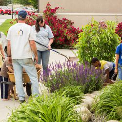 Doug and Deanne Walker spruce up the yard with their children. Deanne Walker said her secret to keeping the house neat and tidy is that everyone has to pull their part of the load.