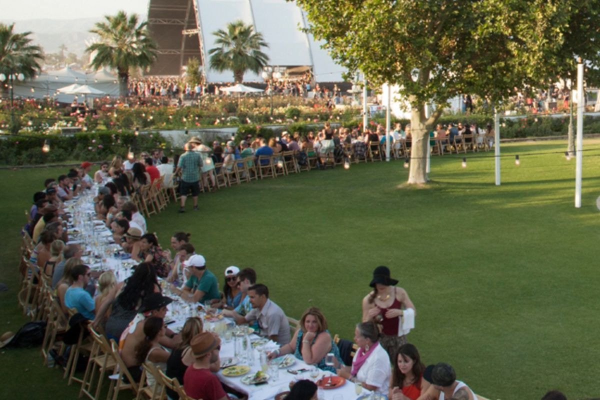 A long tableclothed-table full of diners in an outdoor field