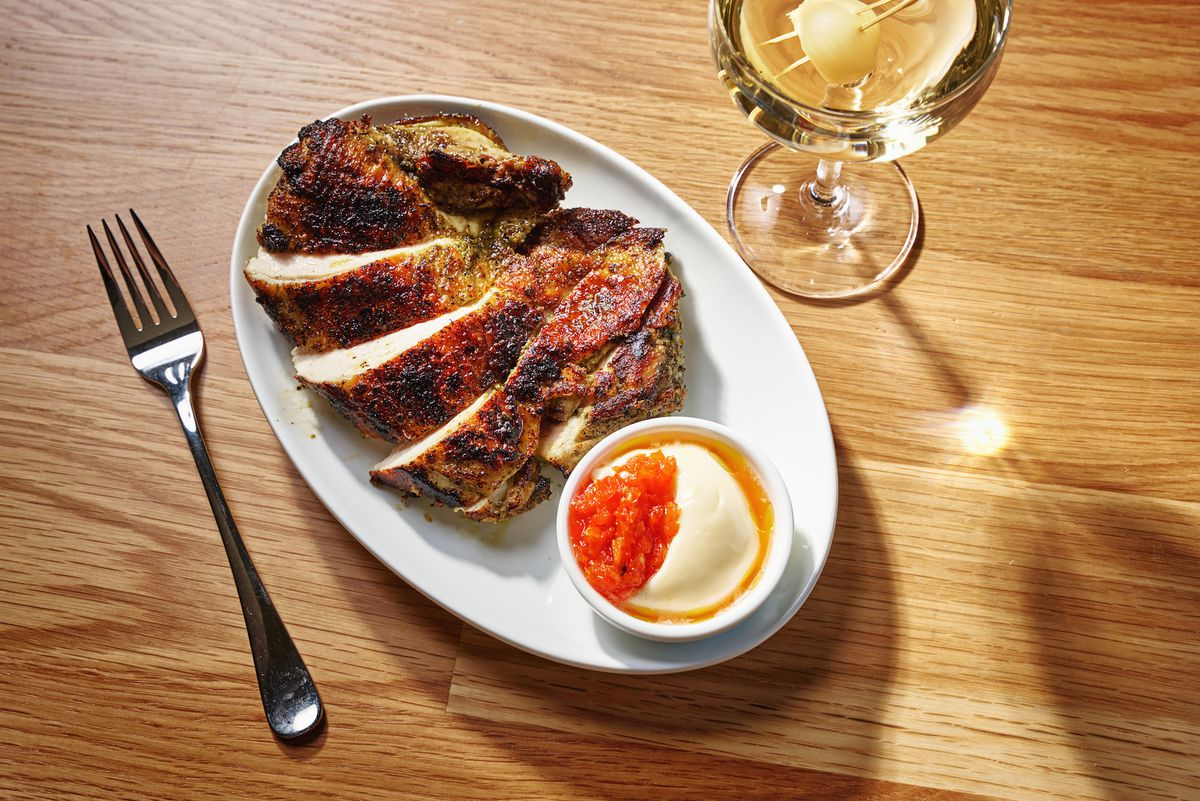 A grilled, brownish piece of chicken sliced up into pieces and placed on a table next to a glass of alcohol