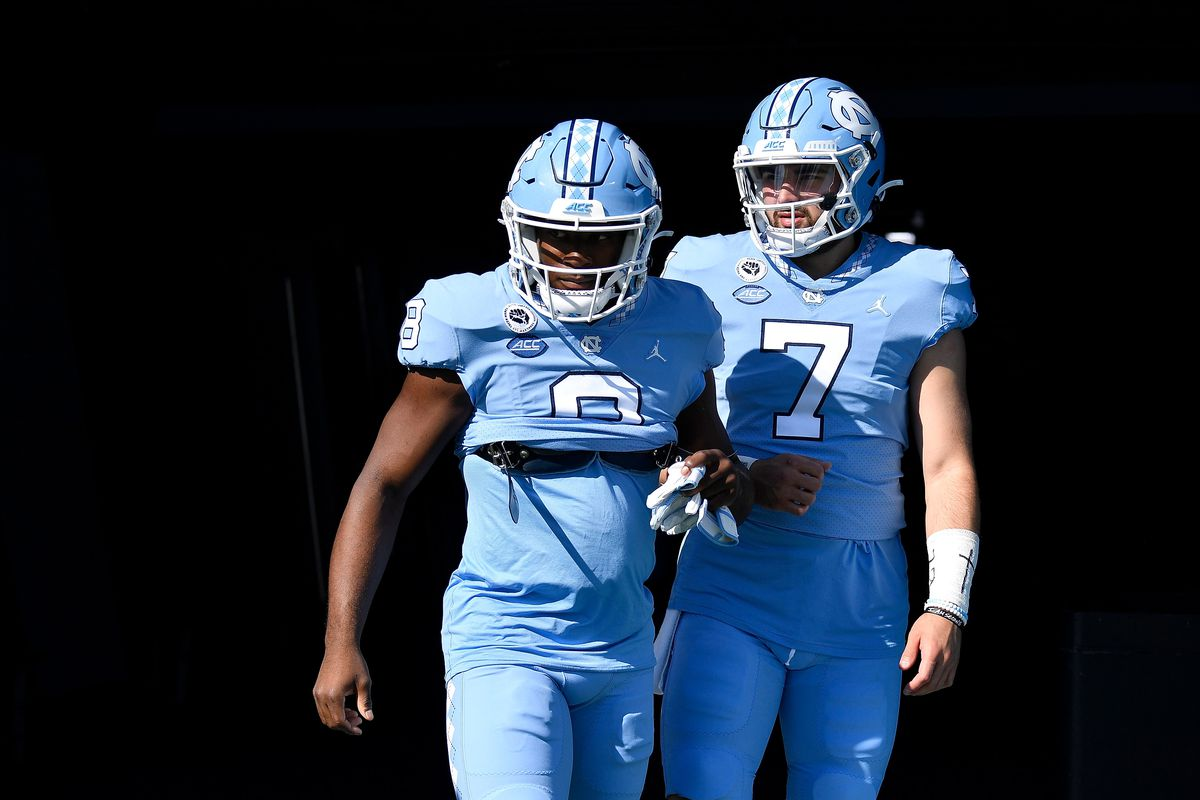 Michael Carter and Sam Howell of the North Carolina Tar Heels take the field for their game against the North Carolina State Wolfpack at Kenan Stadium on October 24, 2020 in Chapel Hill, North Carolina.