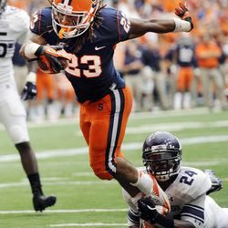 Syracuse's Julian Whigham (23) scores while being tripped up by Northwestern's Ibraheim Campbell (24) during the first quarter of an NCAA college football game in Syracuse, N.Y., Saturday, Sept. 1, 2012.