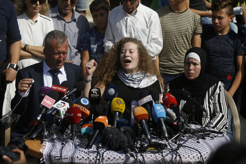 Ahed Tamimi speaks sitting between her father Bassam and mother Nariman during a press conference on the outskirts of the West Bank village of Nabi Saleh on Sunday, July 29, 2018. Palestinian protest icon Ahed Tamimi and her mother Nariman returned home t