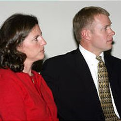Bronco Mendenhall and his wife, Holly, at a news conference.