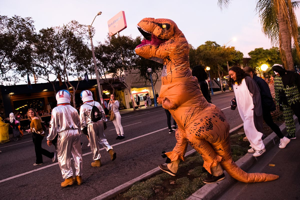 People wearing Halloween costumes, including astronauts and a dinosaur, walk through a closed street at sunset.