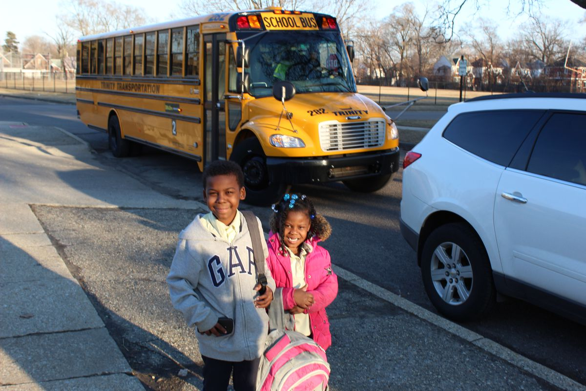 Two young children stand in front of a yellow school bus.