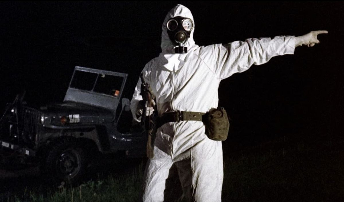 The Crazies: a man in a hazmat suit points off camera while holding a gun