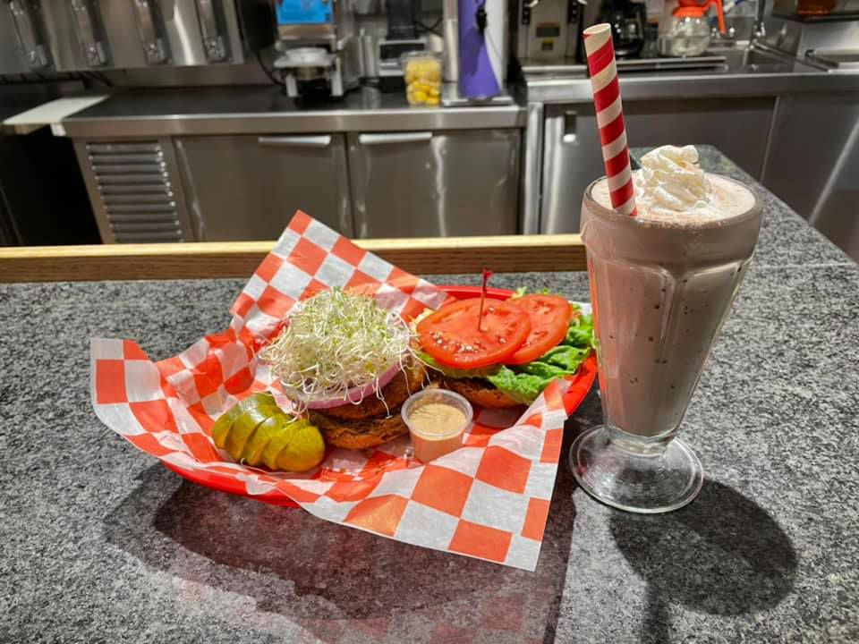 Checkered paper-lined basket with an open-faced veggie burger topped with a heap of sprouts, beside a tall milkshake on a formica diner counter