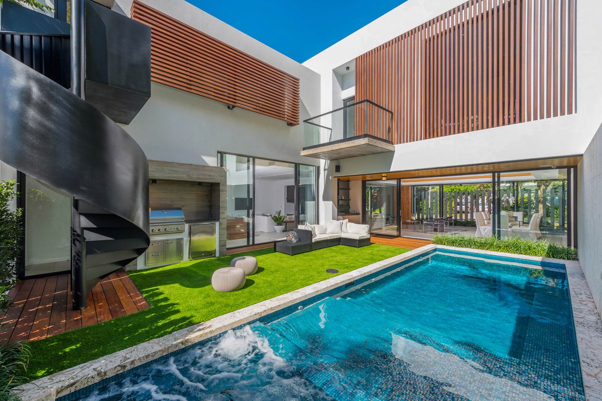 A tropical modern home's courtyard with artificial grass and a heated saltwater pool