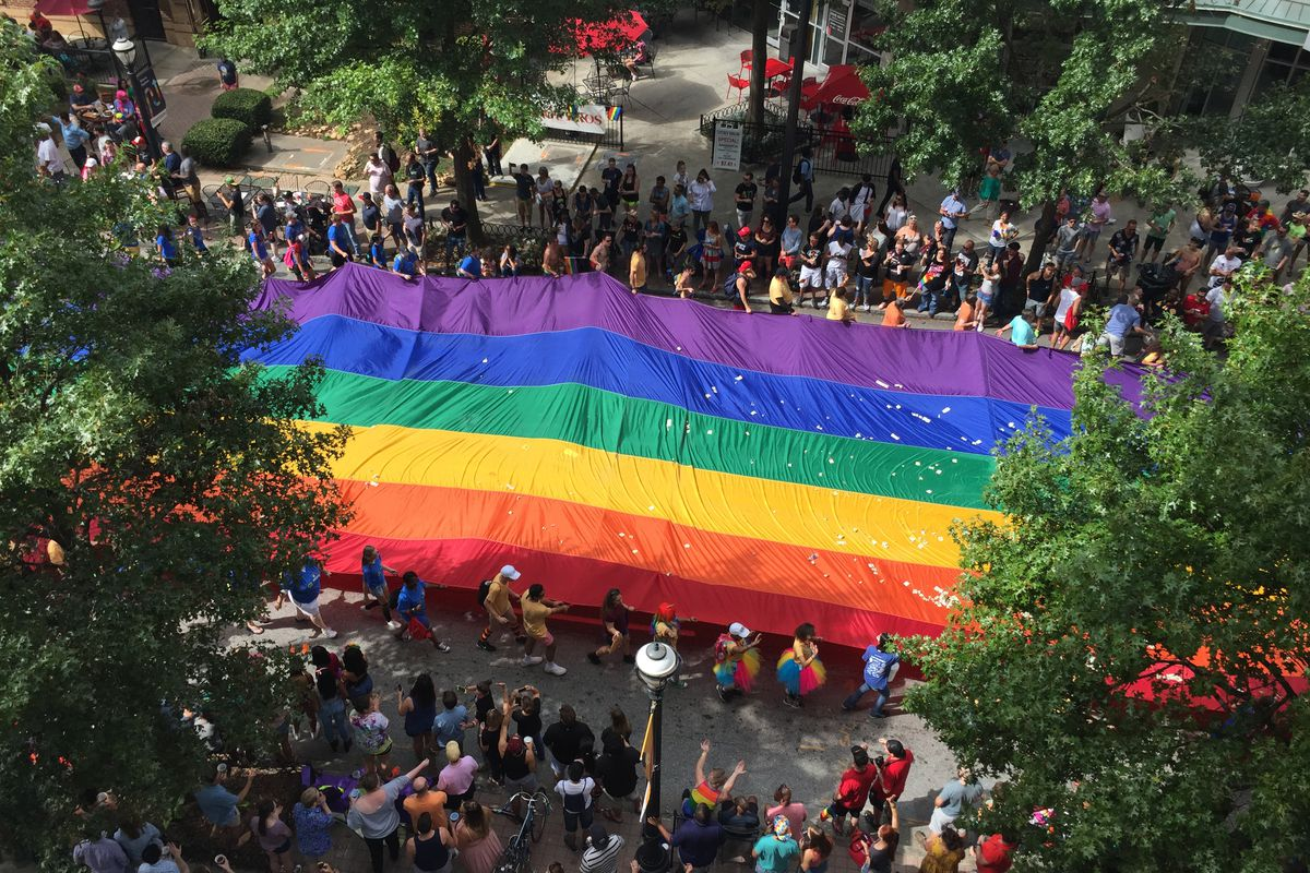 An aerial view of a flag taking up all four lanes of Peachtree.