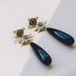 18 karat gold 'Revival' earrings with emeralds, diamonds, and black onyx, $13,650