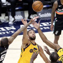 San Antonio Spurs guard Dejounte Murray (5), Utah Jazz center Rudy Gobert (27) and Utah Jazz guard Miye Oni (81) reach for the rebound during an NBA game at Vivint Smart Home Arena in Salt Lake City on Monday, May 3, 2021. The Jazz won 110-99.
