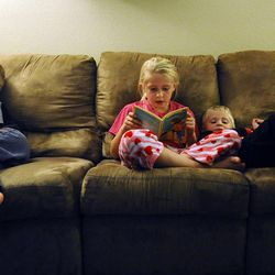 6-year-old Porter Burton plays with one of his toys as 8-year-old Mykenzie reads before bedtime with 3-year-old Logan by her side at home Sept. 25.