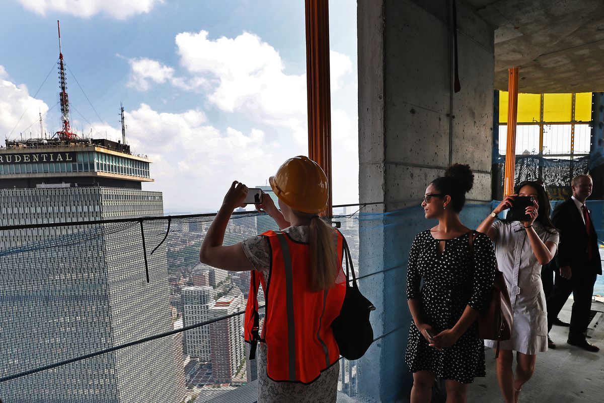 People milling about and snapping photos from an open floor of an under-construction skyscraper.