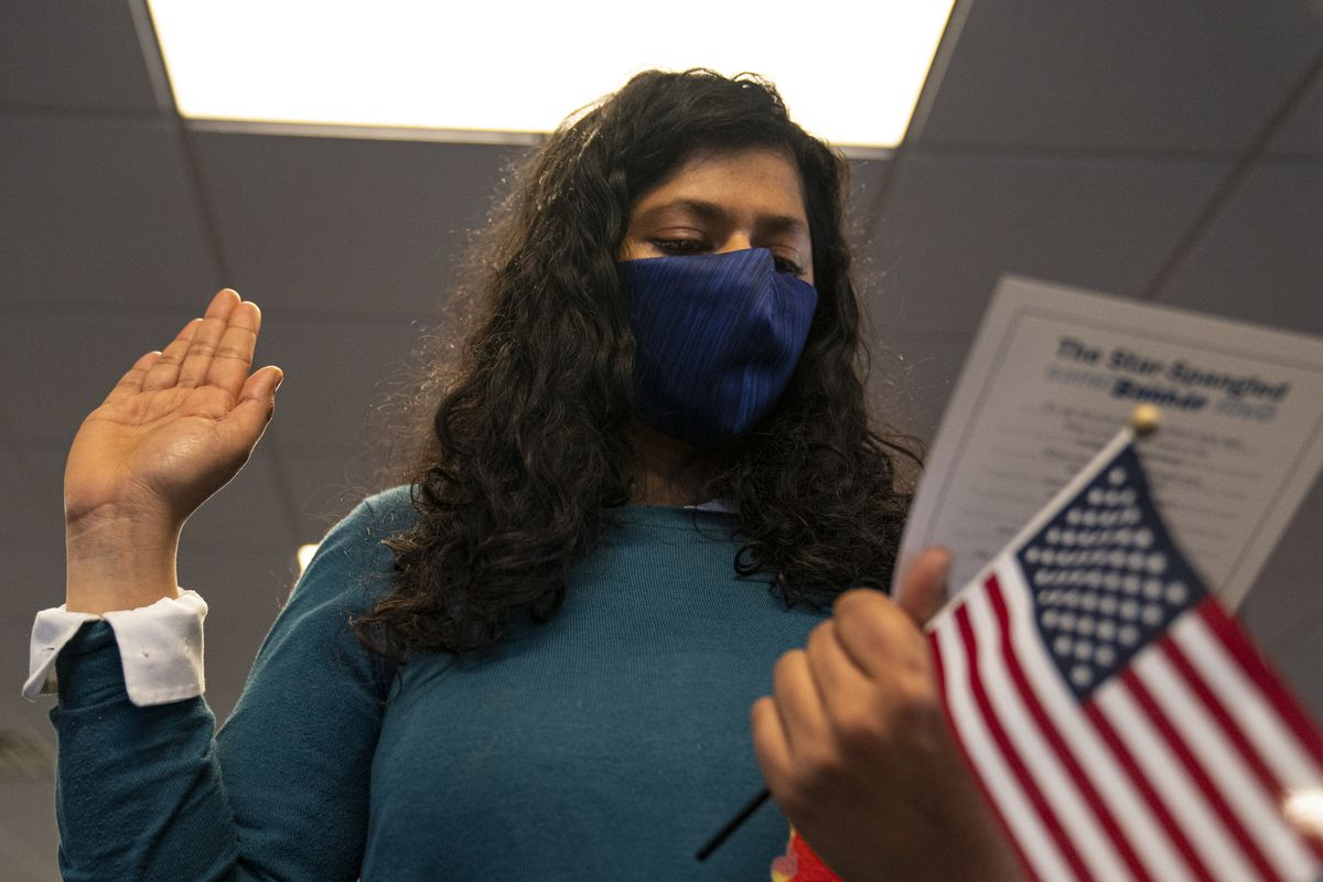A person in a face mask holds up their right hand while looking at a printed sheet of paper in their left hand, which also holds a small American flag on a stick.