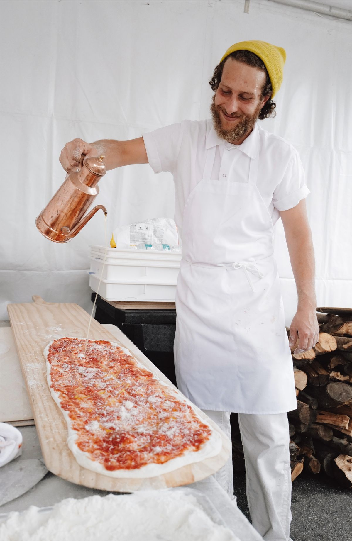 Hans Fama makes pizza for Forno Fama in a tent.
