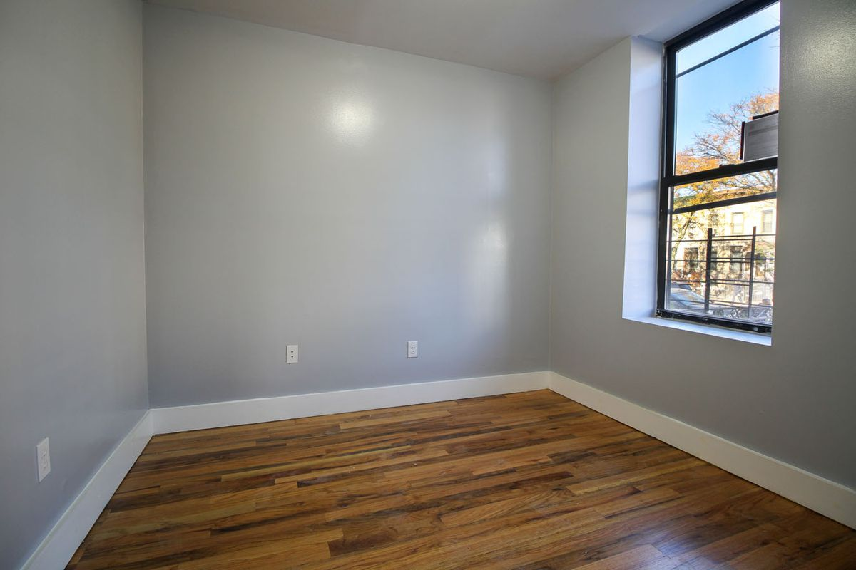 A bedroom with grey walls and hardwood floors.