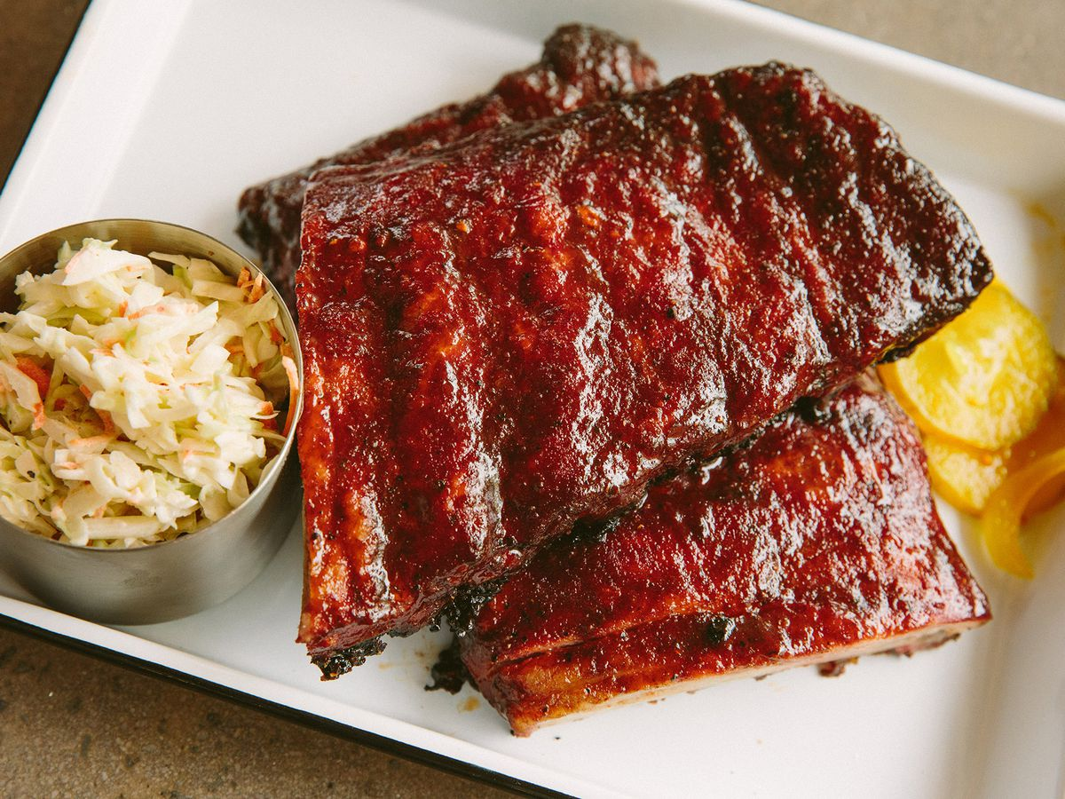 A plate of glossy red ribs with sides of slaw and pickles at the Porch in Medford.
