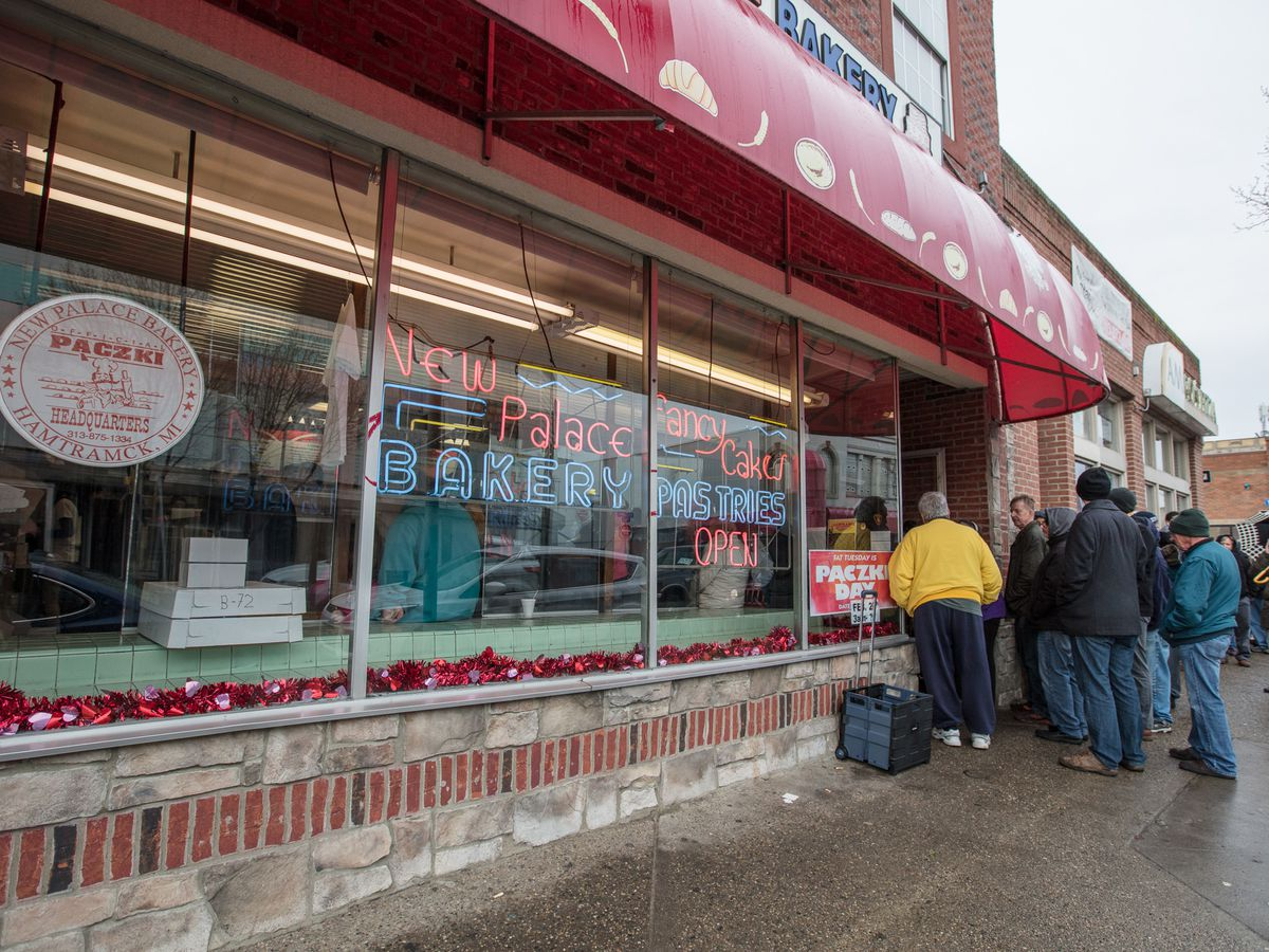 Customers line up beneath the red awning of New Palace Bakery on a cloudy Paczki Day.