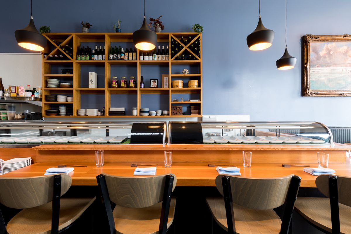 The sushi bar at Chisai Sushi Club with wooden cubbies on the wall behind.