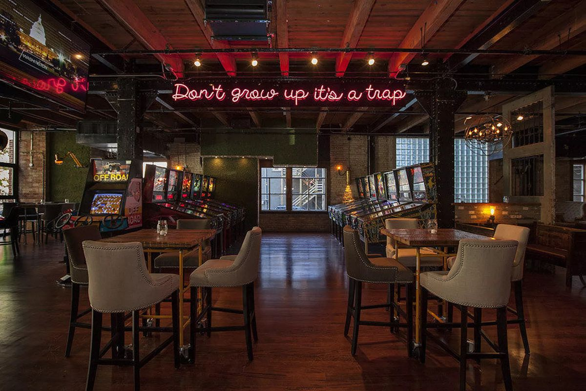 """A dark bar interior with lines of arcade games and a neon sign overhead that reads """"Don't grow up it's a trap."""""""