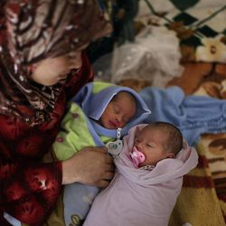 In this Friday, Sept. 7, 2012, photo, Syrian Fatimah Abdullah, 29, who fled her home in Marea 15 days ago, due to Syrian government shelling, sits next to her 4 days old twin  Ahmad and Bayan, who were born in a Turkish hospital and brought back with her to the border where they take refuge at the Bab Al-Salameh border crossing, in hopes of entering one of the refugee camps in Turkey, near the Syrian town of Azaz. The days are still hot across the fertile plains of northern Syria, but at night there is a hint of a chill an ominous harbinger of winter's approach and the deepening of the humanitarian crisis gripping a country wracked by civil war.
