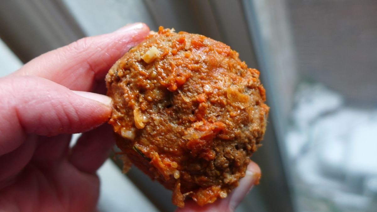 A hand holds a giant meatball daintily in front of a window.