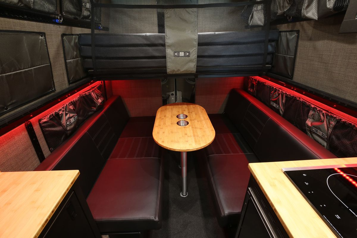 The interior of a camper van. There are seats, a table, a kitchenette with a stove, and various storage components.