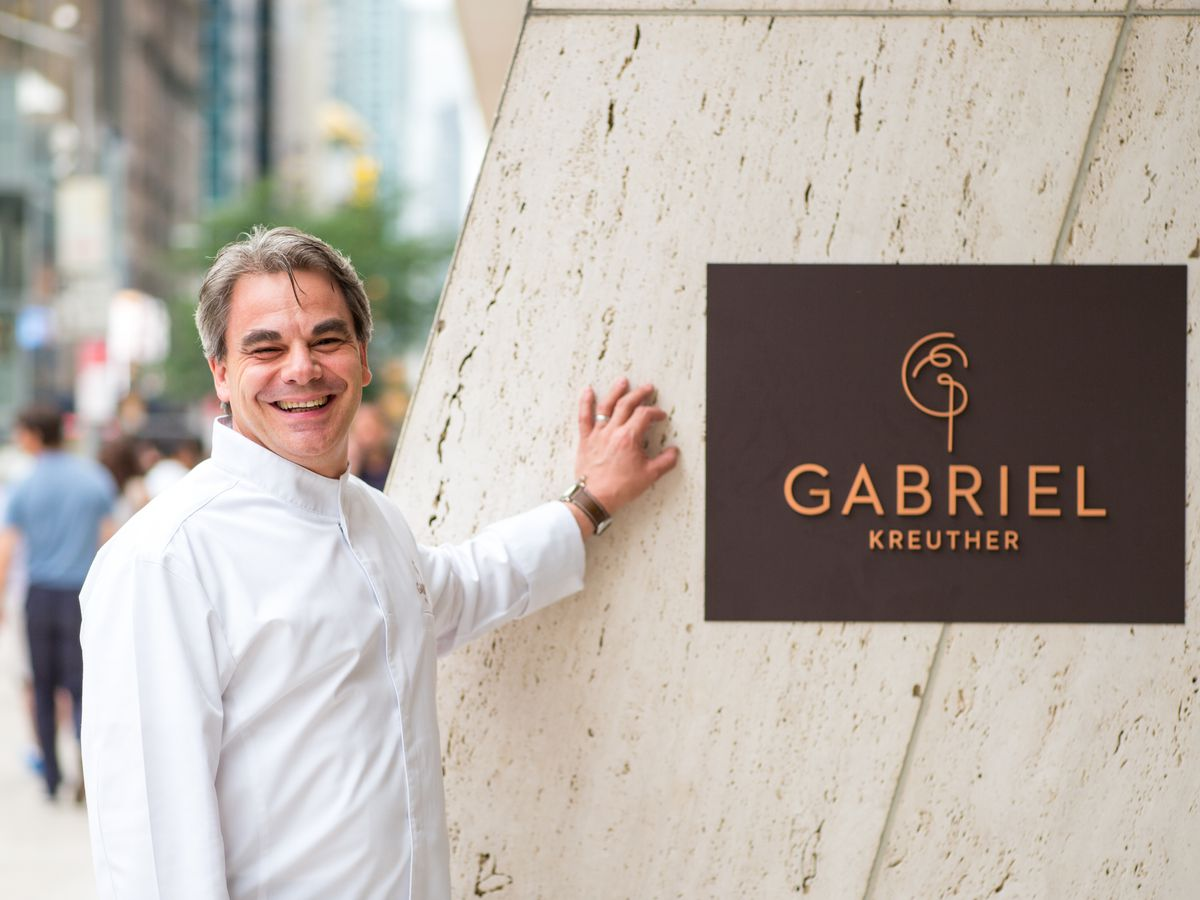 Gabriel Kreuther stands in front of a sign that says the name of his restaurant