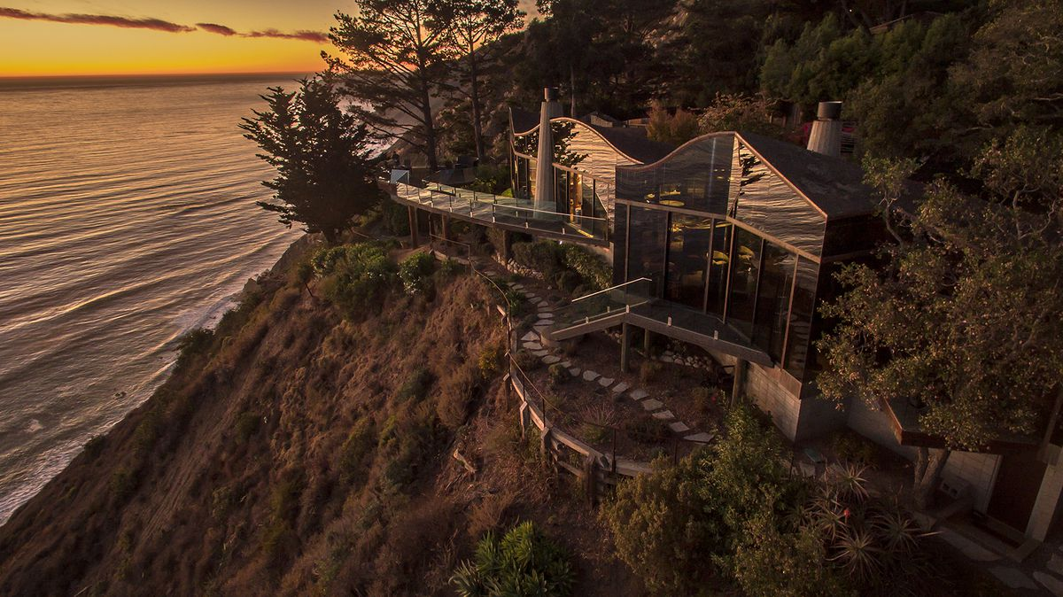 A curving home on a cliff at sunset. There are decks and paths on the home, and the ocean spreads out on the left.