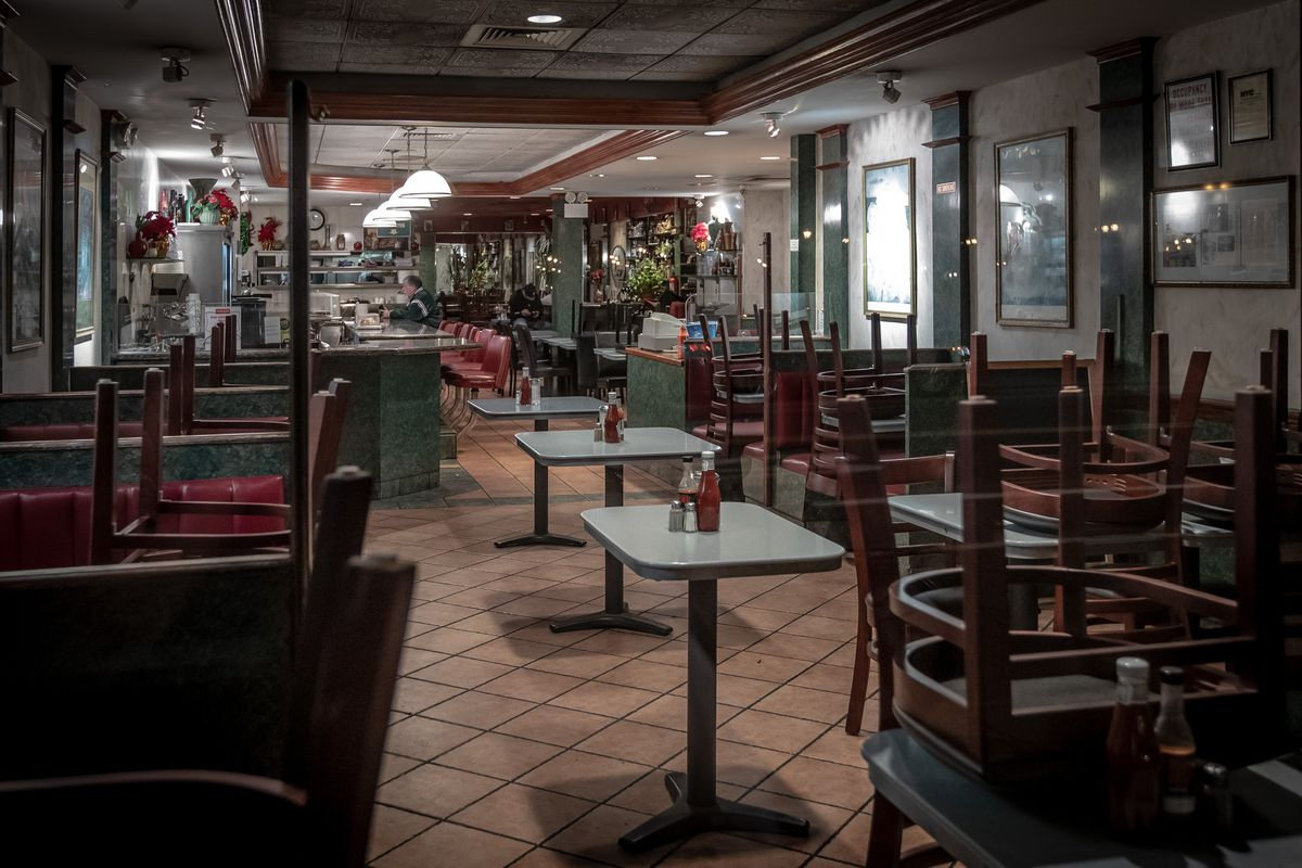 The interior of a closed diner, where chairs are overturned onto tables and bottles of ketchup, salt, and pepper are still propped onto tables
