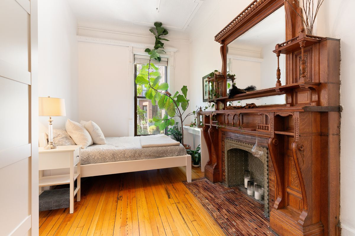 A room with a white bed, large houseplant, and huge wooden fireplace.