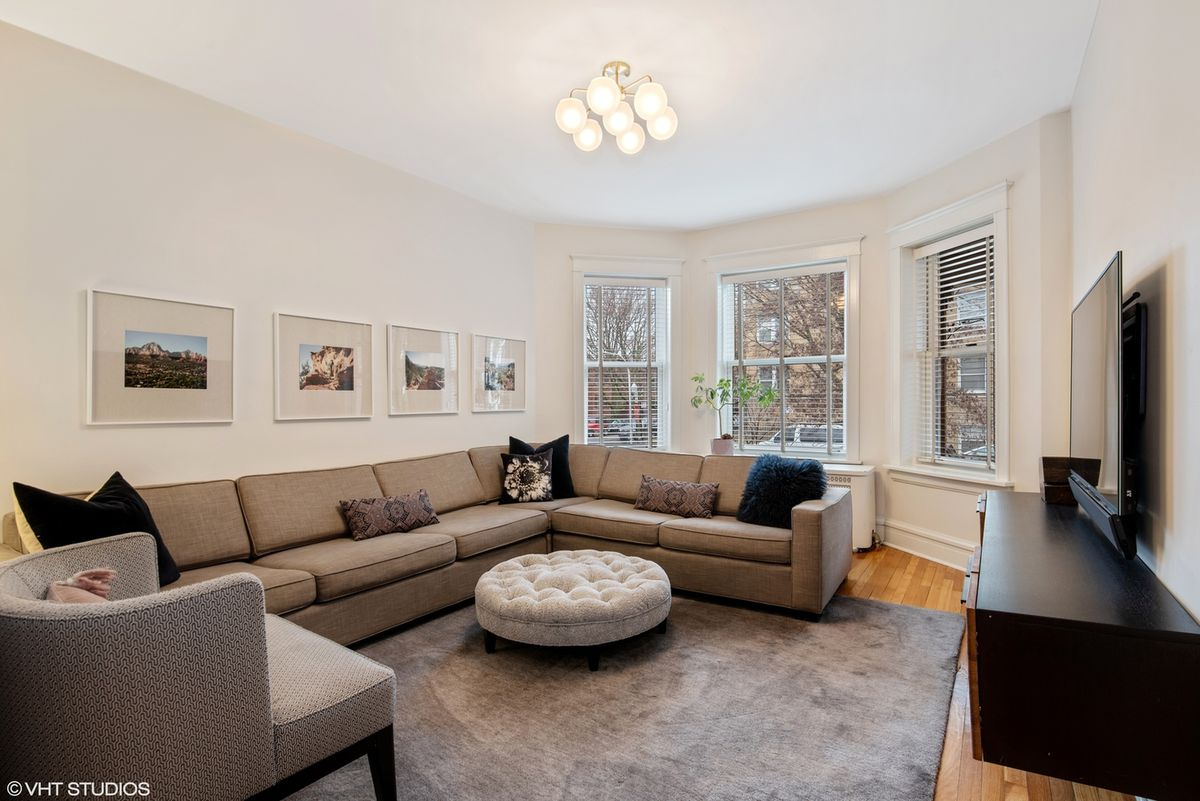 A living room with a sectional, glass shade light fixture, a bay window, and a tv.