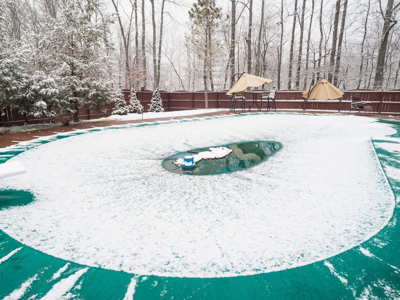 In-ground home pool covered in winter with snow.