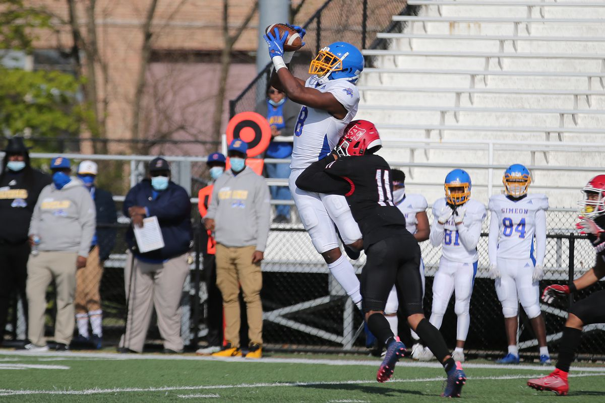 Simeon's Malik Elzy (8) takes a big hit as he catches and hangs on to the ball.