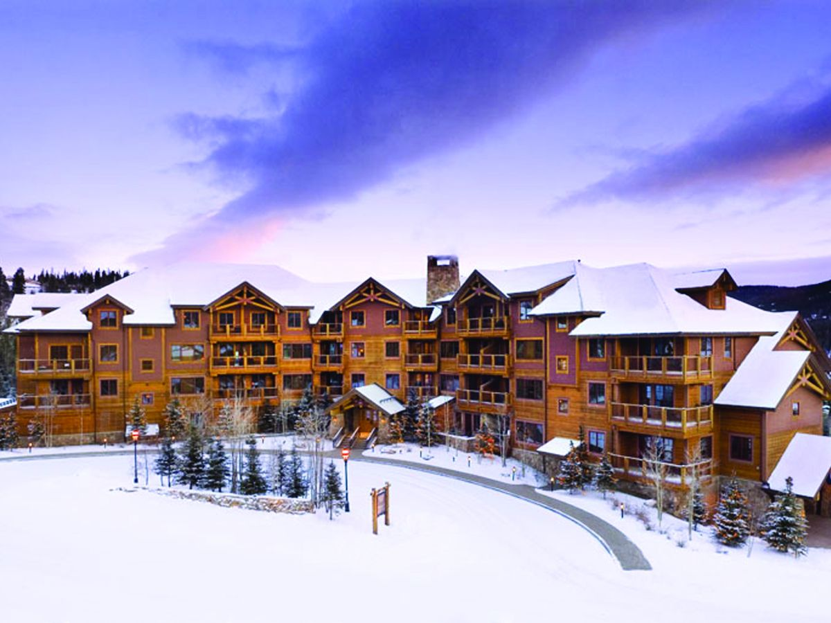 A large, lodge-style timber hotel sits on a snowy driveway with a purple sunset behind it.