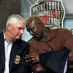 Basketball Hall of Fame inductee Karl Malone, right, leans to speak with fellow inductee Robert Hurley, Sr. during the enshrinement news conference at the Hall of Fame Museum in Springfield, Mass. Friday.