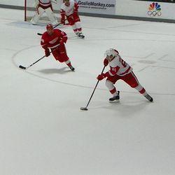 Xavier Ouellet skates the puck with Landon Ferraro in pursuit
