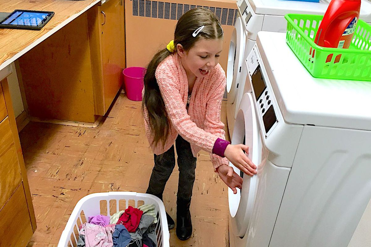 Morgan Pohl, a third-grader at Doull Elementary in Denver, prepares to do a load of laundry at school.