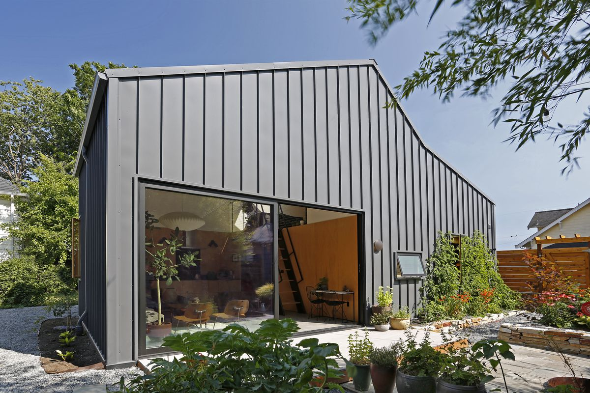Single-story home with angled ceiling and black metal panels. A large sliding door opens to a garden.