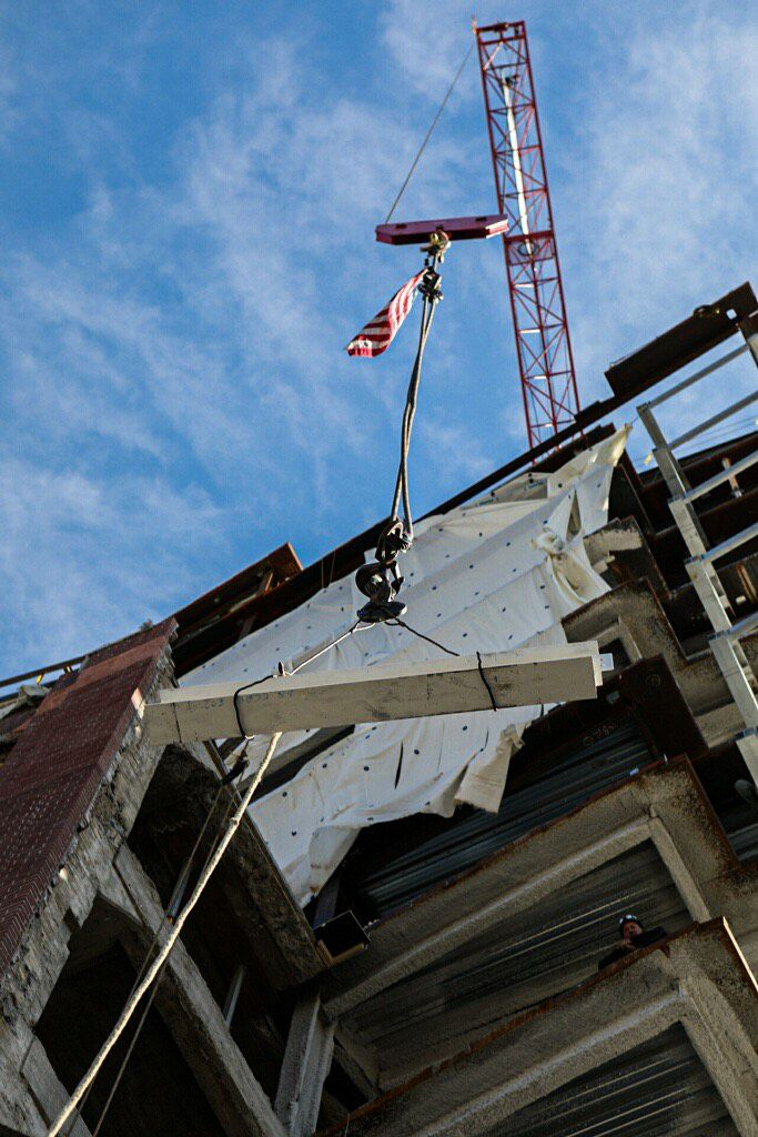 A crane with a flag putting a beam into place on a 13-story building.