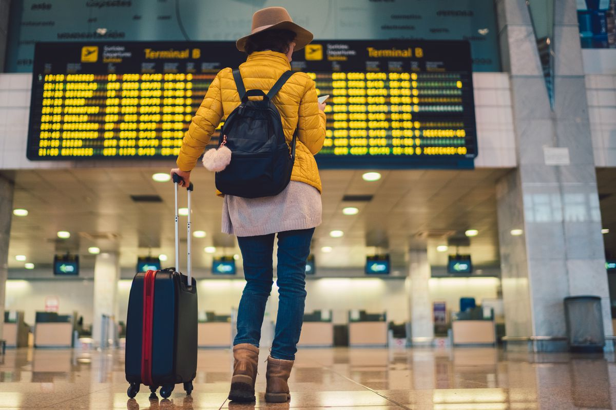 A young woman with a suitcase beside her stands at an airport flight arrivals and departures display.