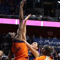 Connecticut Sun's Chiney Ogwumike (13) wins a jump ball over Washington Mystics' Stefanie Dolson (31).