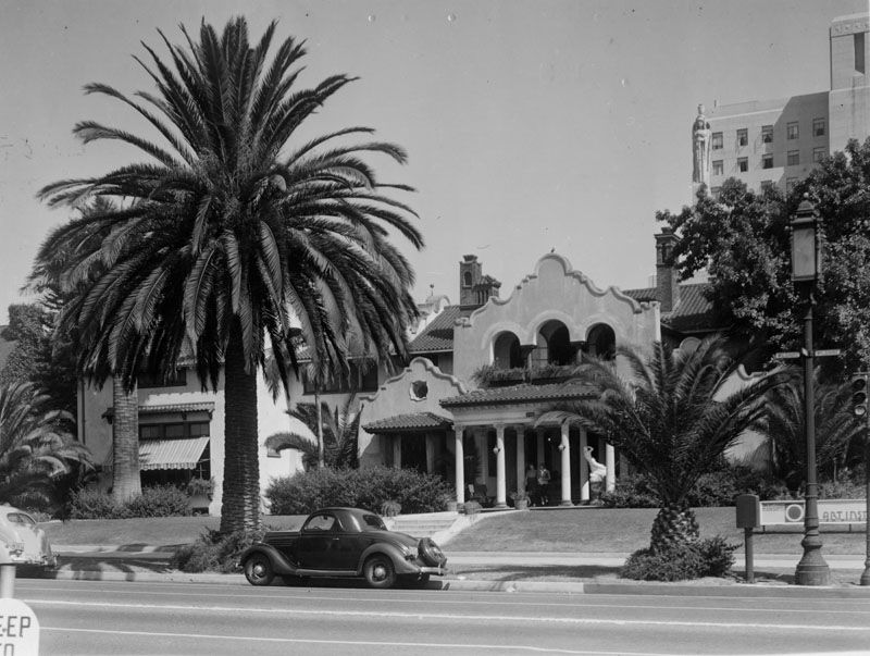 A large house with columns near the entrance. There are palm trees, a yard, and a car parked in front of the house. The house has a garage and a path leading to the entrance.